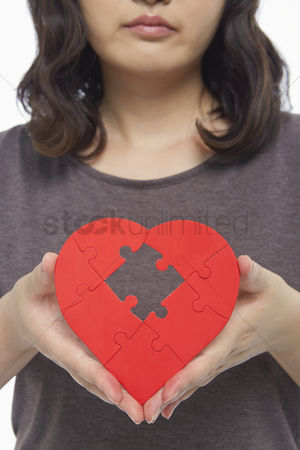 Heart : Sad woman holding up a red heart shape with a missing puzzle piece