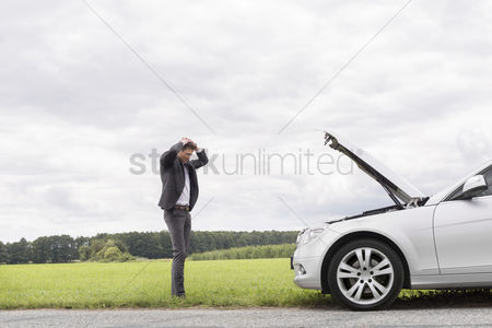 On the road : Sad young businessman standing with hands on head near broken car at countryside