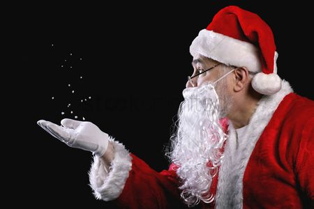 Black background : Santa claus playing with snow