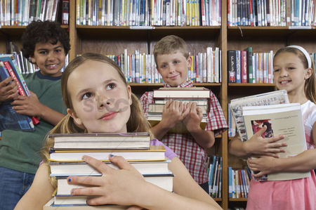 Pupil : School children holding books in library