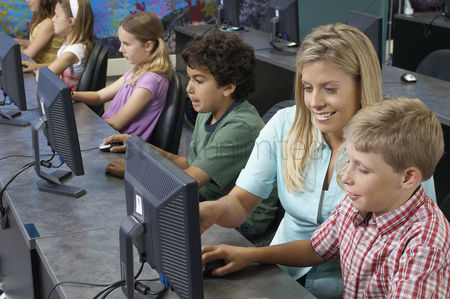 Teacher : School children using computers with teacher in classroom