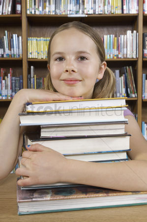 Pupil : School girl hugging books in library portrait