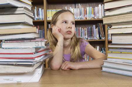 Pupil : School girl sitting at desk with books in library