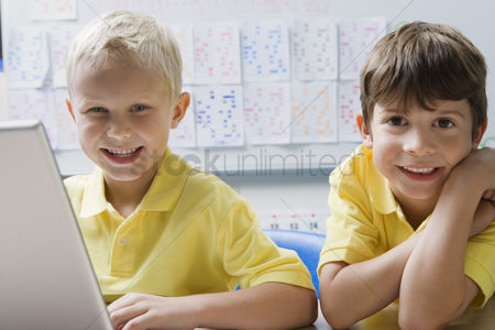 Posed : Schoolboys using a laptop
