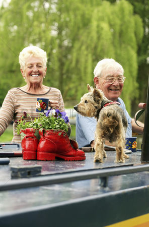 Friends : Senior couple and their pet dog on the houseboat