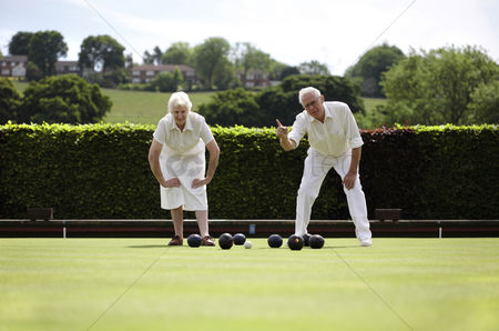 Resting : Senior couple lawn bowling in the bowling green