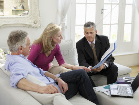 Business suit : Senior couple sitting on sofa with financial advisor elevated view