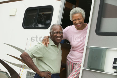 On the road : Senior couple with motor home  portrait