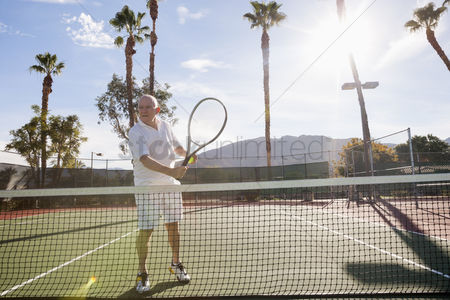 Bald : Senior male tennis player holding racket on court