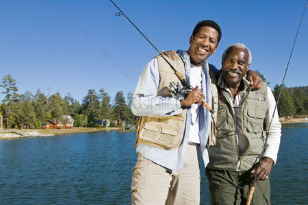 Masculinity : Senior man and son holding fishing rods by lake smiling  portrait