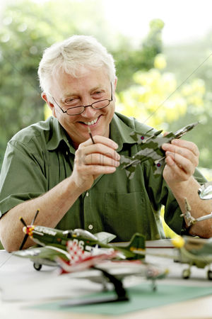 Sets : Senior man building model airplane
