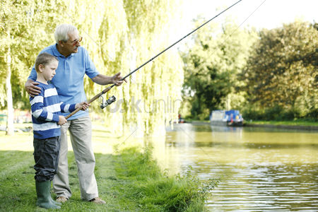 Grass : Senior man fishing with his grandson