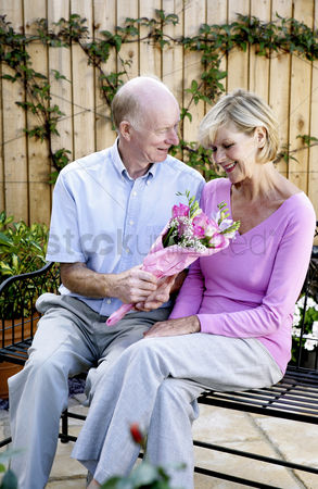 Celebrating : Senior man giving his wife a bouquet of flowers