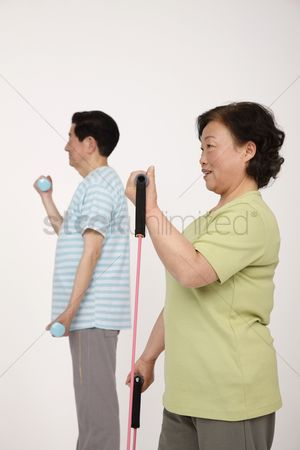 Dumbbell : Senior man lifting weight while senior woman is exercising with elastic band