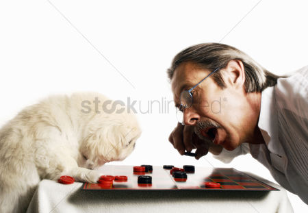 Thought : Senior man playing checkers with his dog