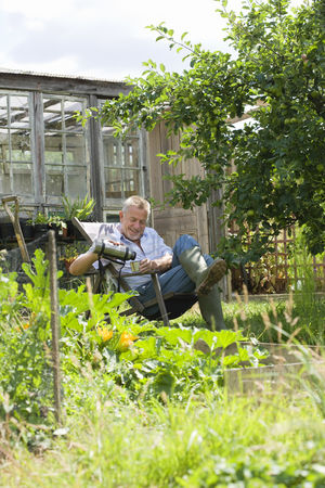 Greenhouse : Senior man pouring drink sitting in garden