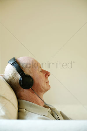 Aging process : Senior man sitting on the couch listening to music on the headphones