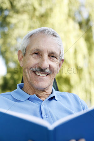 Resting : Senior man smiling at the camera while holding a book