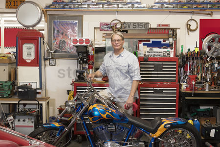 Transportation : Senior man standing behind motorcycle in automobile repair shop