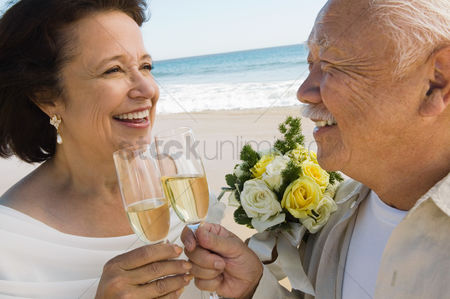 Toasting : Senior newly weds toasting champagne at beach  close-up