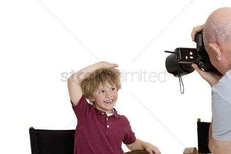 Bald : Senior photographer clicking school kid sitting on chair over white background