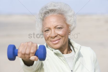 Dumbbell : Senior woman excercising with dumbbell on beach