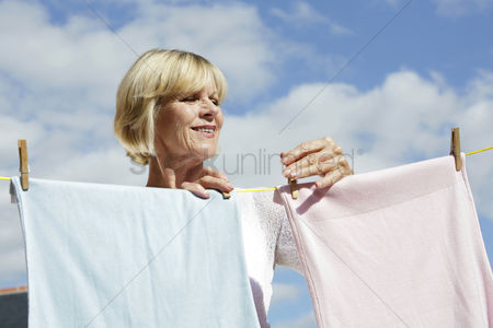 Seniors : Senior woman hanging clothes on the clothesline