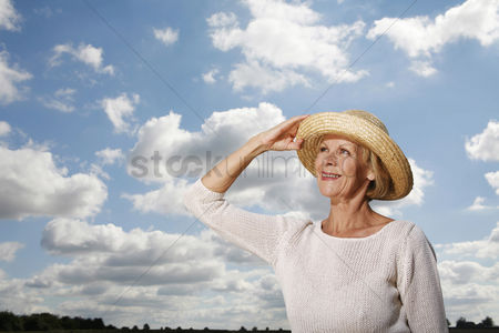 Outdoor : Senior woman holding her hat while looking up