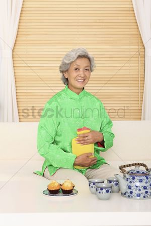 Tea pot : Senior woman holding hot-water bottle  smiling at the camera