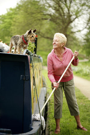 Houseboat : Senior woman looking at her dog while mopping her houseboat