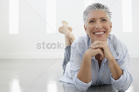 Senior women : Senior woman lying on floor in home