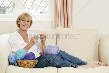 Aging process : Senior woman sitting on the couch knitting