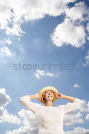 Aging process : Senior woman smiling while holding her hat