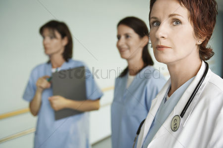 Posing : Serious physician with nurses in hospital corridor focus on physician portrait