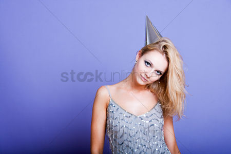 Fashion : Sexy blonde party girl wearing silver dress and party hat