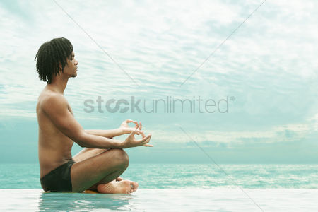 Outdoor : Side shot of an african american man meditating on the beach