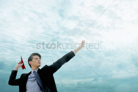 Outdoor : Side view of a man in business suit throwing a red paper plane