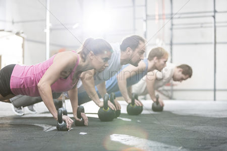 Women : Side view of determined people doing pushups with kettlebells at crossfit gym