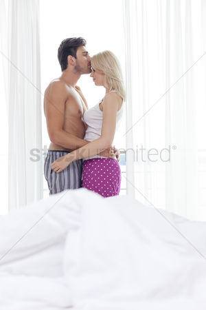 Kissing : Side view of loving young man kissing woman on forehead in hotel room