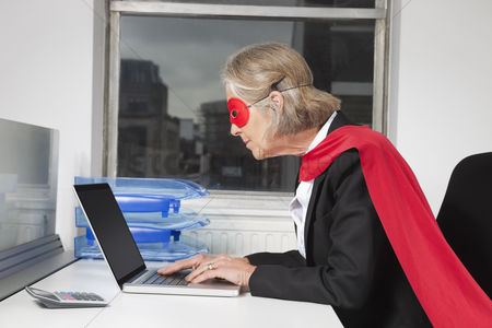 Technology : Side view of senior businesswoman in superhero costume using laptop at office desk