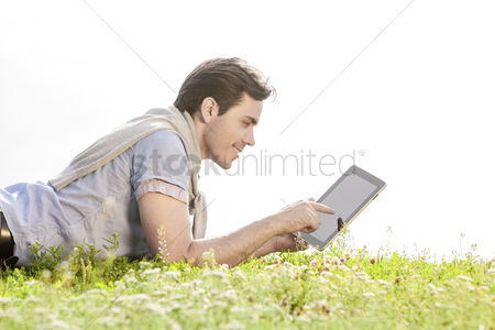 Grass background : Side view of young man using digital tablet while lying on grass against clear sky