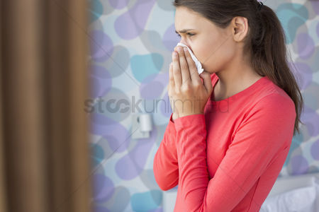 Cold : Side view of young woman blowing nose at home