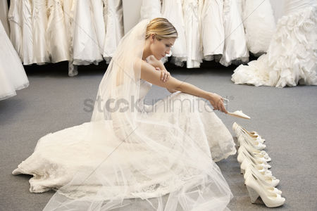 Shopping : Side view of young woman in wedding dress confused while selecting footwear