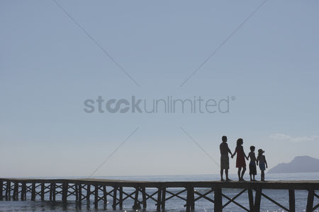 Pre teen : Silhouettes of parents and children  6-11  on jetty