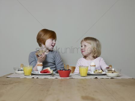 Interior background : Sisters sit eating breakfast together and talking