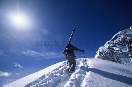 Winter : Skier hiking to mountain summit