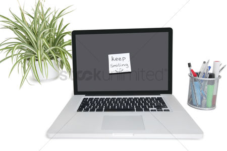 Technology background : Smiley face sticky note on laptop with office supplies and pot plant