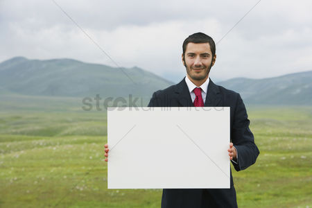 Remote : Smiling businessmen standing in mountain field holding blank sign front view