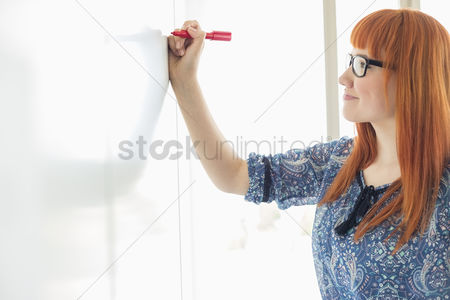 Pen : Smiling businesswomen writing on whiteboard in creative office