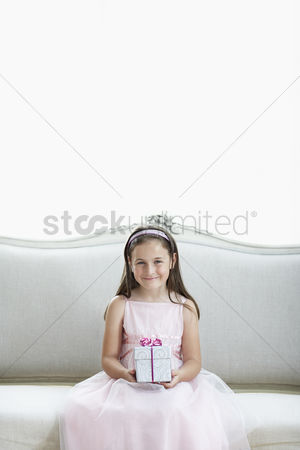 Dance : Smiling girl in tutu sitting on sofa holding gift portrait